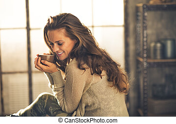 Portrait of relaxed young woman with cup of coffee in loft...