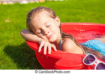 Portrait of relaxing adorable little girl enjoying her vacation in small pool outdoor