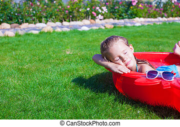 Portrait of relaxing charming little girl enjoying her vacation in small pool