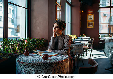 Portrait of retro style lady sitting with book