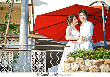 portrait of romantic bride and groom with red umbrella