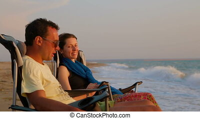 Portrait of Romantic Couple Relaxing On Folding Chairs Under Sunshades At Beach