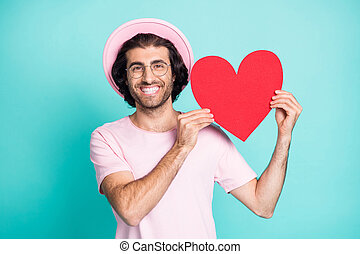 Portrait of romantic funny guy showing paper heart wear pink cap t-shirt spectacles isolated on teal color background