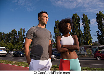 Portrait of romantic pretty couple on fitness session, outside town background