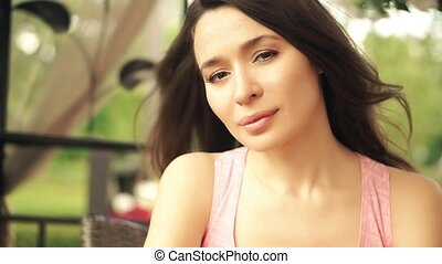 Portrait of romantic young brunette sitting at the table. Slow motion clip