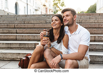 Portrait of romantic young couple smiling and looking aside together while sitting on stairs outdoors with paper cup