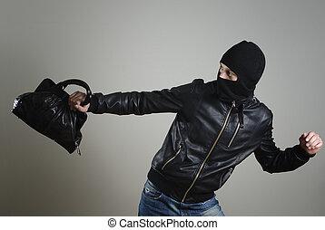 Portrait of running male burglar with a handbag.