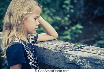 Portrait of sad blond little girl sitting on the bridge