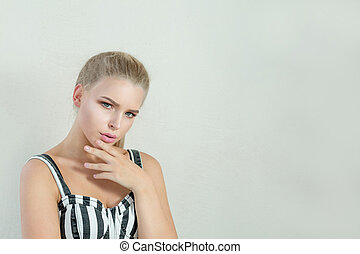 Portrait of sad blonde girl with natural makeup posing at white background. Space for text