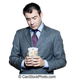 Portrait of sad businessman holding money box in studio on...