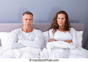Sad Couple Sitting On Bed