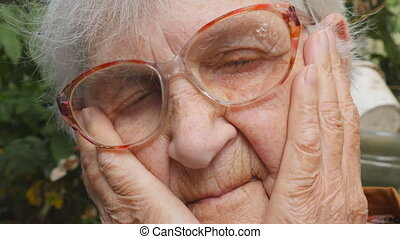 Portrait of sad grandmother with emotions and feelings. ?ld woman looking with sorrowful expression outdoor. Grandma keeping hands at her face. Close up Slow motion