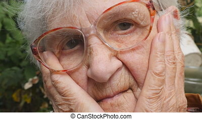Portrait of sad grandmother with emotions and feelings. Old woman looking at camera with sorrowful expression outdoor. Grandma keeping hands at her face and sighing heavily. Close up Slow motion