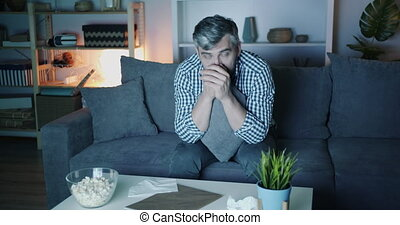 Portrait of sad guy wiping eyes with tissue watching TV at...