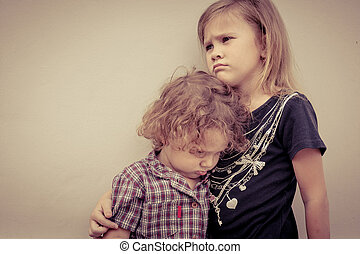 Portrait of sad little girl and little boy standing near wall in the day time