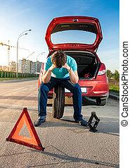 sad man sitting on spare wheel near broken car - Portrait of...