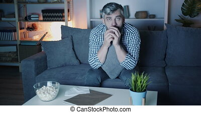 Portrait of sad man watching drama on TV at home wiping eyes...