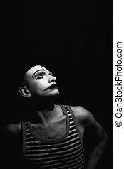 Portrait of sad mime on black background