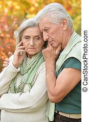 Portrait of Sad senior couple in park