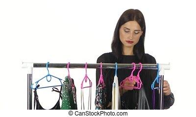 Portrait of sad woman choosing dresses at a boutique. White