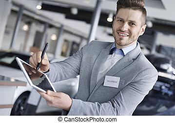 Portrait of salesman holding digital tablet