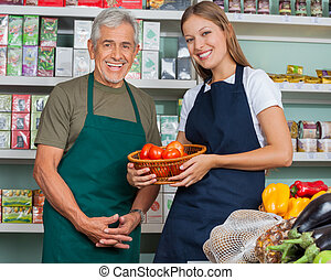 Portrait of saleswoman holding vegetable basket with male colleague in grocery store