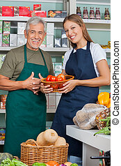 Portrait of saleswoman holding vegetable basket standing with male colleague in supermarket