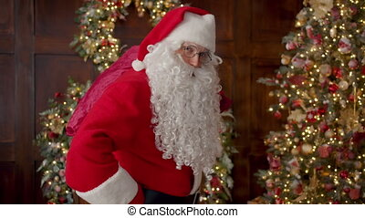 Portrait of Santa bringing bag with gifts to Christmas tree winking and looking at camera in decorated house. Celebrations and presents concept.