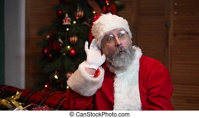 Portrait of Santa Claus holding his hand near his ear, trying to listen to interesting news. Old man with beard in red suit and hat against the background of Christmas tree with toys and lights. Happy New Years evening. Slow motion.