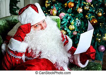 Portrait of Santa Claus reading Christmas letters