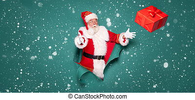 Portrait of Santa Claus with a red gift on a green studio background.