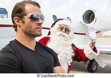 Portrait of Santa waving hand with bodyguard in foreground against private jet at airport terminal