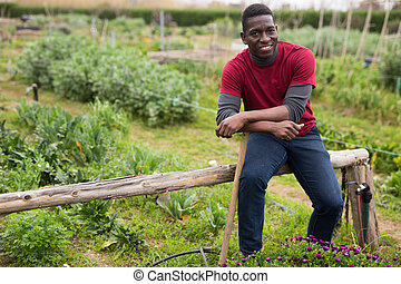 Portrait of satisfied african american gardener in the backyard of a village house
