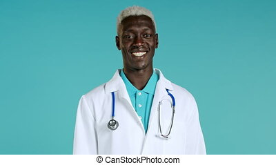 Portrait of satisfied african doctor in professional medical coat showing yes sign by head. Man permits, treats approvingly. Doc man isolated on blue background. High quality 4k footage