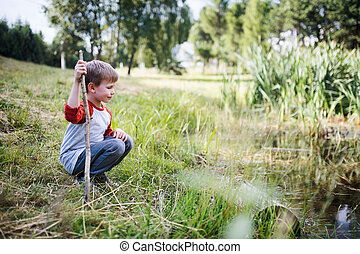 Portrait of school child on field trip in nature, looking at pond.