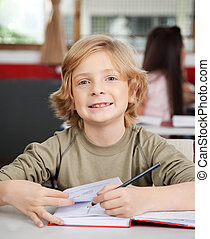 Portrait Of Schoolboy Writing In Book At Desk
