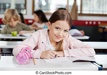 Portrait Of Schoolgirl Drawing In Book