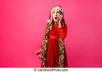 Portrait of schoolgirl girl in Santa hat and tinsel on neck, emotionally talking on phone with surprised facial expression isolated on red background