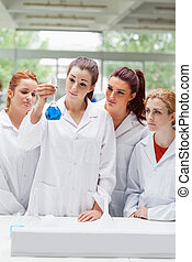 Portrait of science students looking at a flask