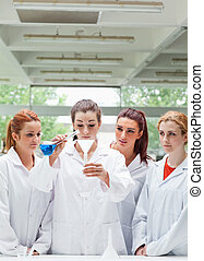 Portrait of science students pouring liquid in a flask