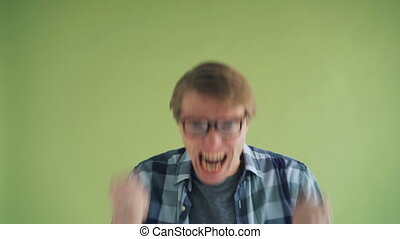 Portrait of screaming young man mad hipster yelling on green...