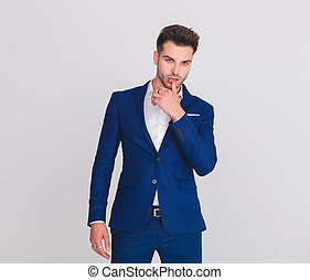 portrait of seductive man in blue suit touching his lips...