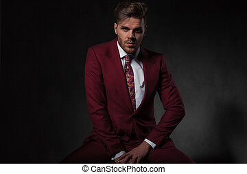 seductive young man wearing grena suit sitting