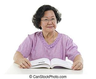 Portrait of Senior adult woman reading book