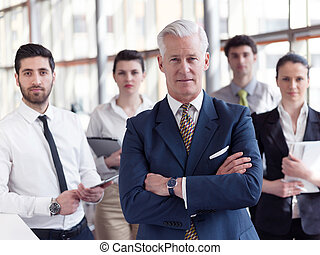 portrait of senior businessman as leader with staff in...