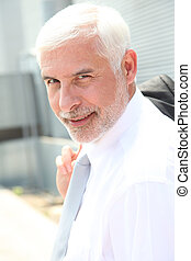 Portrait of senior businessman standing outdoors