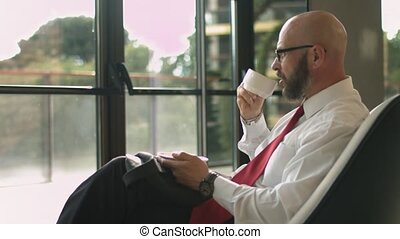 Portrait of senior businessman who looks out the window and...