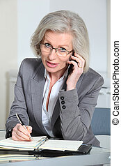 Portrait of senior businesswoman talking on the phone in...