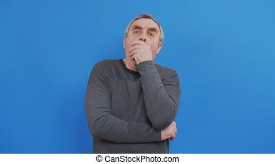 Portrait of senior caucasian man coughing or sneezing into his arm, in slow motion. hygiene and protection during coronavirus covid 19 pandemic