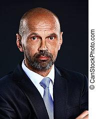Portrait of senior confident businessman on dark background